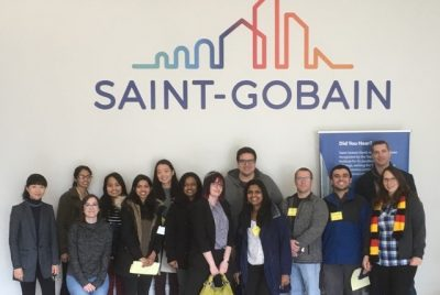 Group in front of Saint-Gobain sign