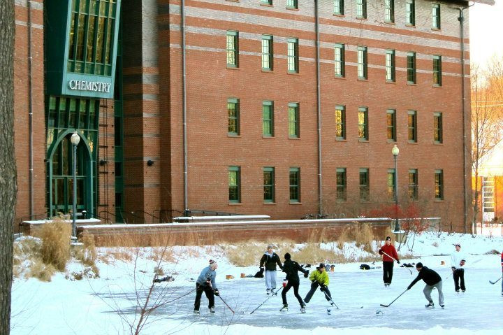 Students playing ice hockey on frozen Swan Lake